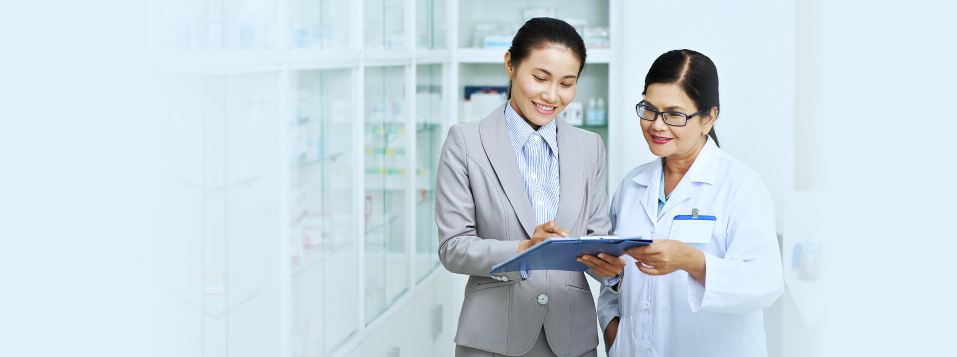 A pharmacist and a woman looking at a paper