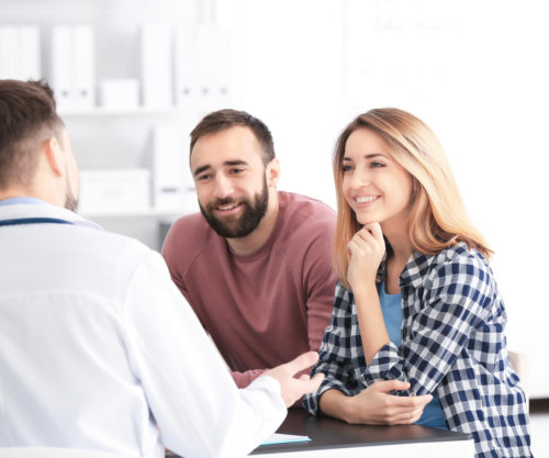 Doctor consulting young couple in clinic